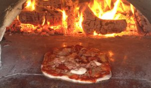 A photo of a pizza cooking in our homemade wood fired pizza oven.